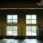 Fitness center using fixed panels in their upper windows to reduce glare. Notice the difference in the glare on the floor between the upper and lower windows